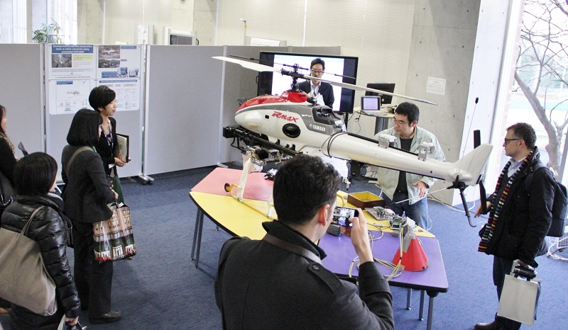 Figure 2. Associate Professor Ohminato explains the use of an unmanned helicopter for placing equipment in dangerous locations. © 2015 The University of Tokyo.