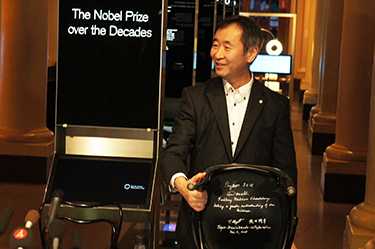 Professor Kajita showing the chair with his signature and that of co-winner Professor Emeritus Arthur B. McDonald
