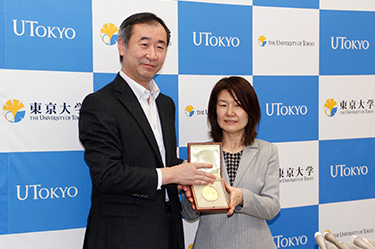 Responding to requests from the media, Professor and Mrs. Kajita pose for photographs holding the Nobel Medal together   (*The Nobel Prize Medal is a copyright and registered trademark of the Nobel Foundation.)