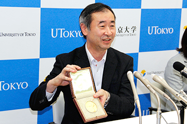 Professor Kajita happily shows his Nobel Medal to the press        (*The Nobel Prize Medal is a copyright and registered trademark of the Nobel Foundation.)