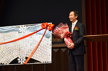 Professor Kajita smiles in front of a postcard-decorated board as he holds a bouquet, both presented to him by the University. Written on the board's small postcards featuring photos of the Super-Kamiokande's photomultiplier tubes are messages from University members