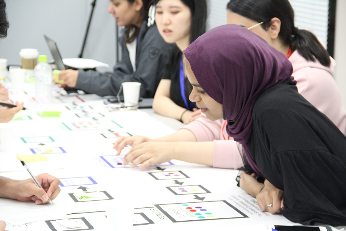 Some students examine a number of game pieces on a table