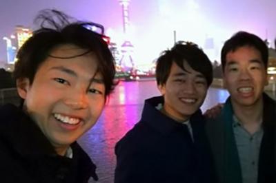 Selfie-style photo of three undergraduate students with cityscape of Shanghai, China in background..