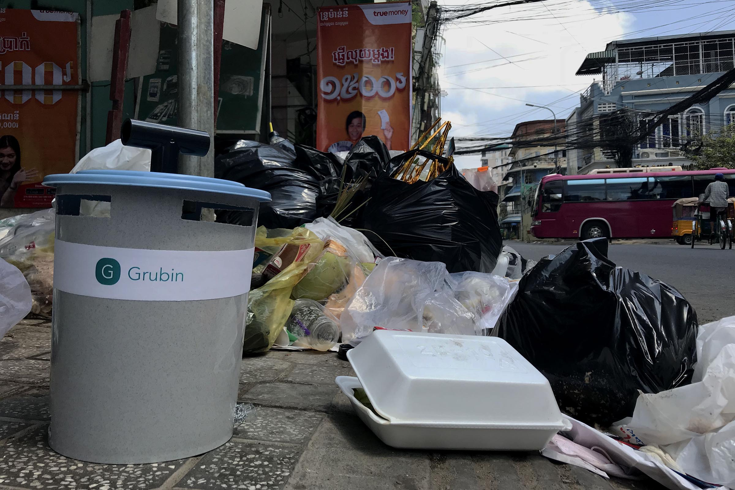 A Grubin in front of a trash pile along a street in Phnom Penh, Cambodia