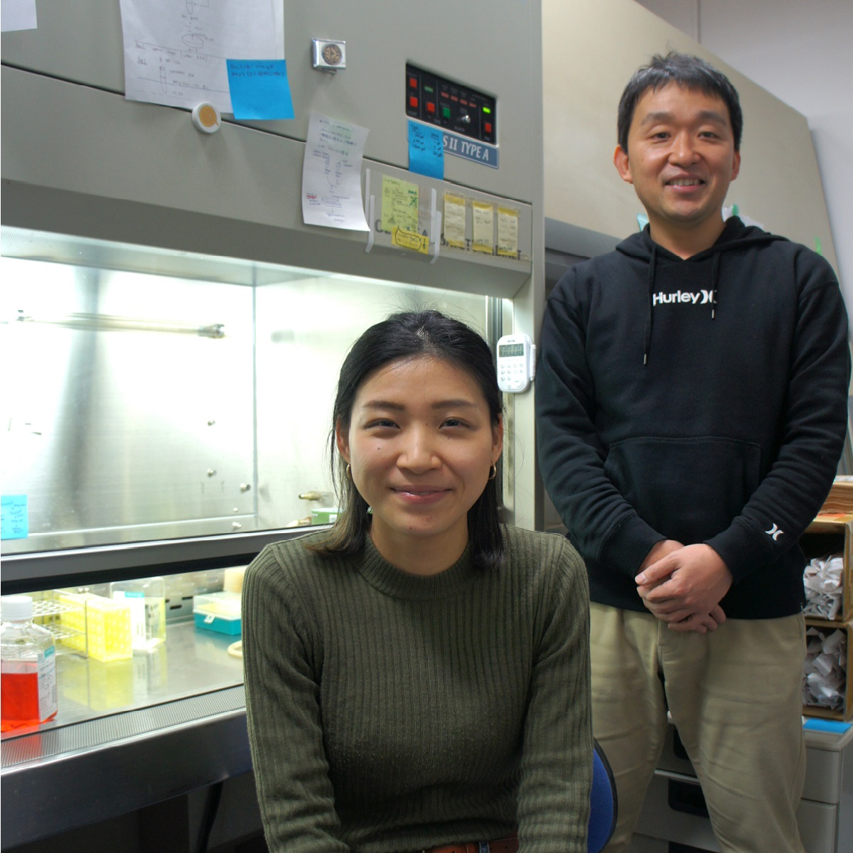 Two scientists in a laboratory, one standing and one sitting infront of a cell culture hood.