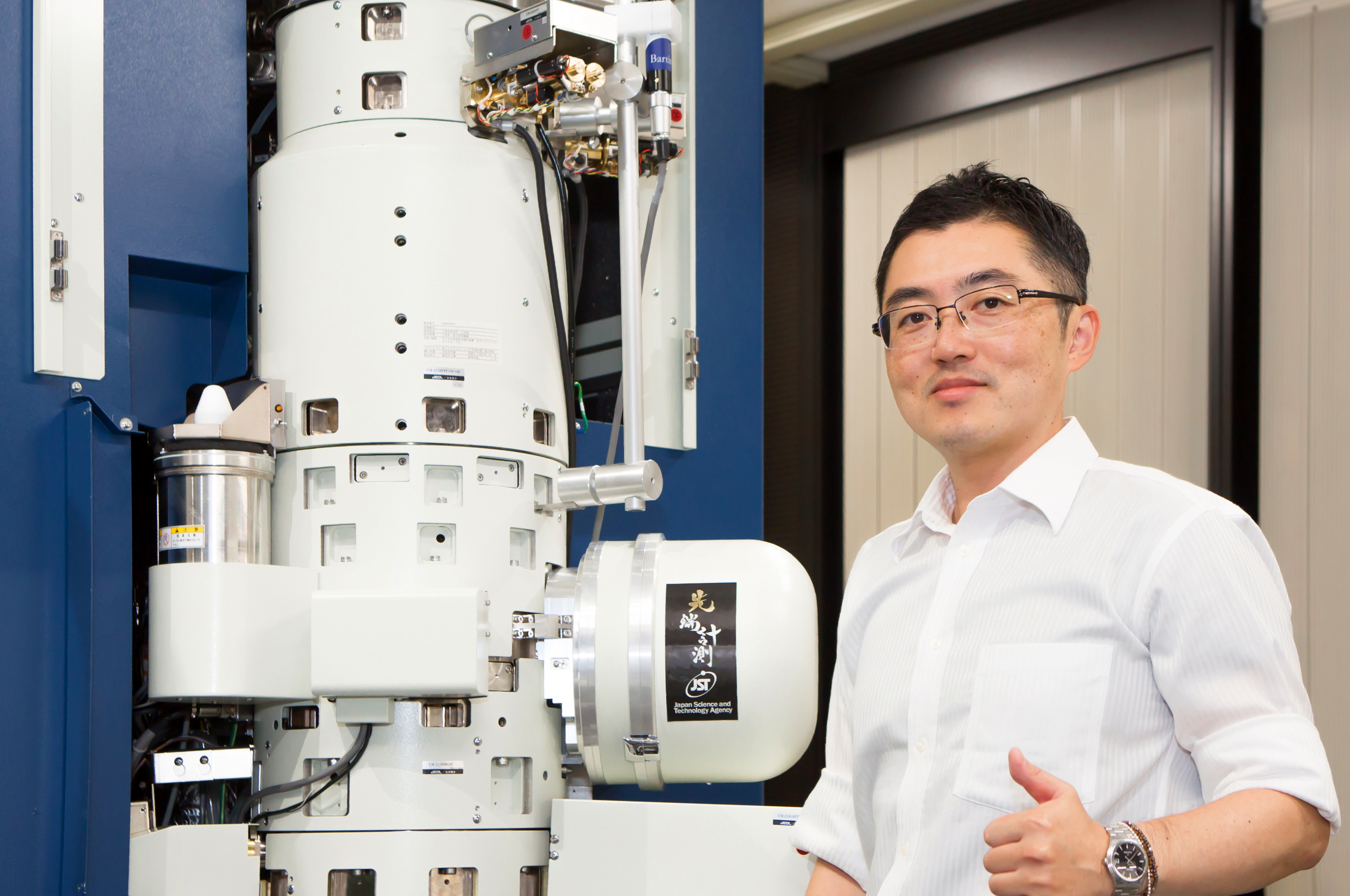 On the left is an electron microscope, a large machine made of white cylinders and covered in electronic components. On the right is a man, Professor Shibata.
