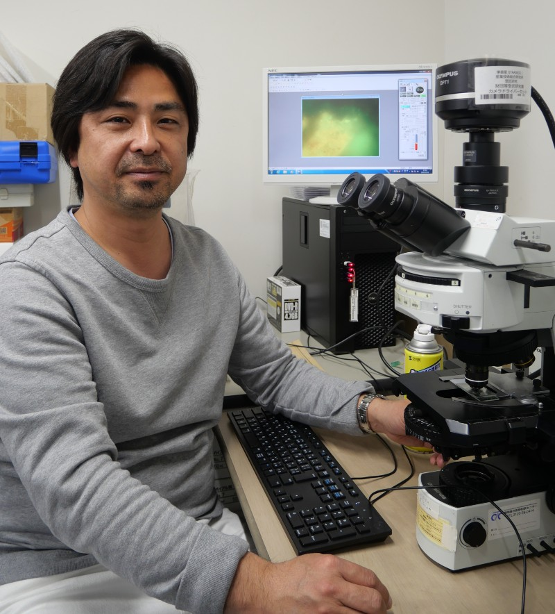 Associate Professor Yohey Suzuki at the microscope with rock sample