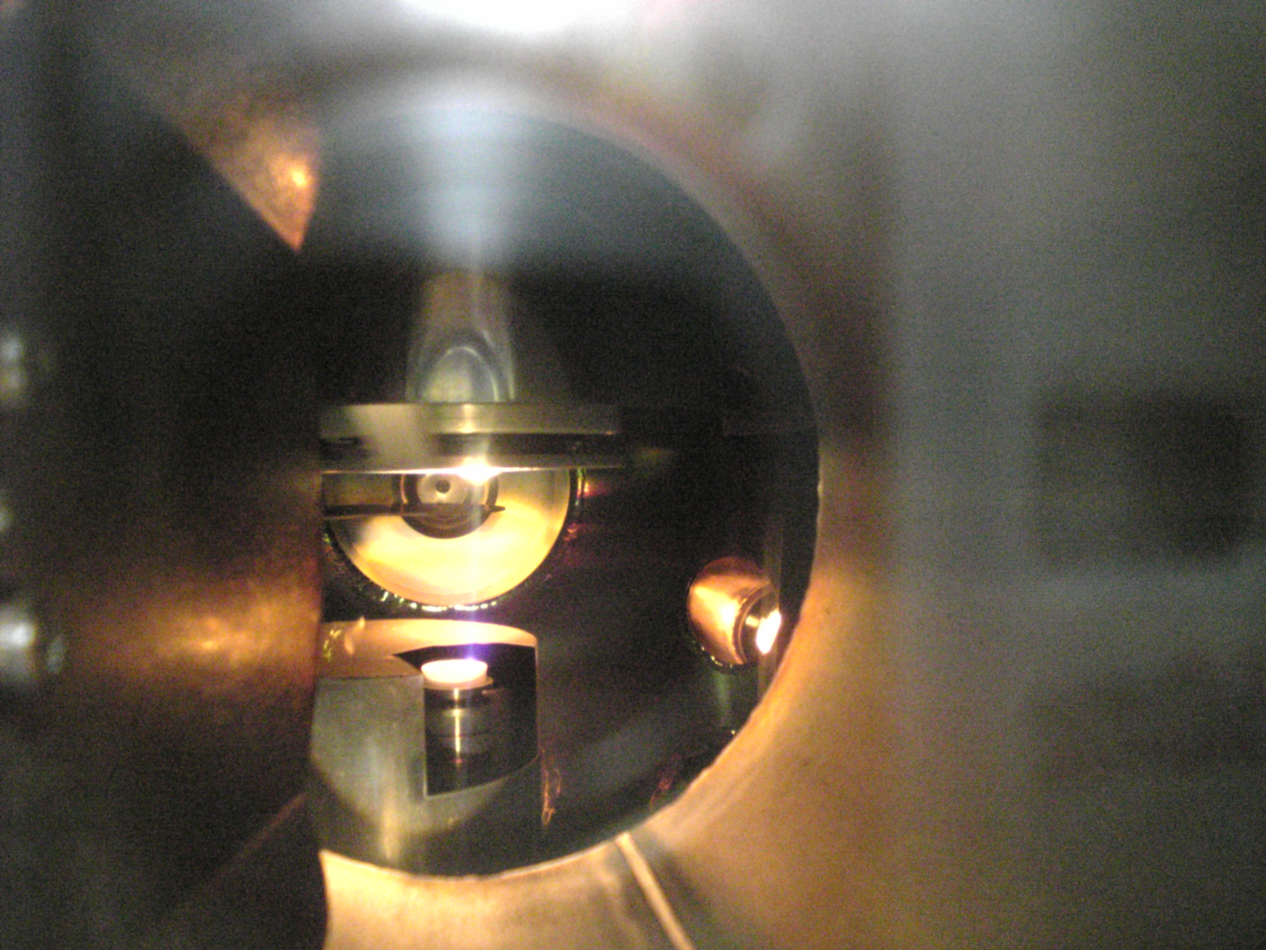 View through a metallic tube, an orange light shines at the end of the tube