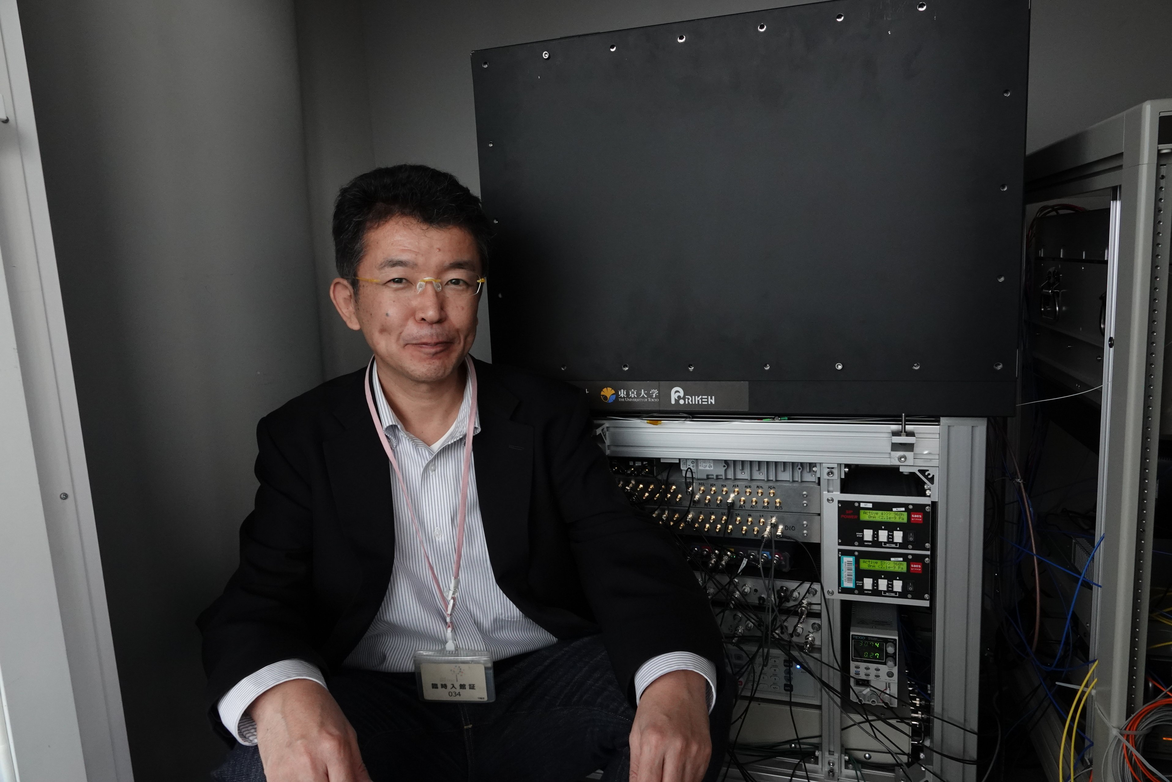 A man sitting next to a grey box with wires coming out of it.